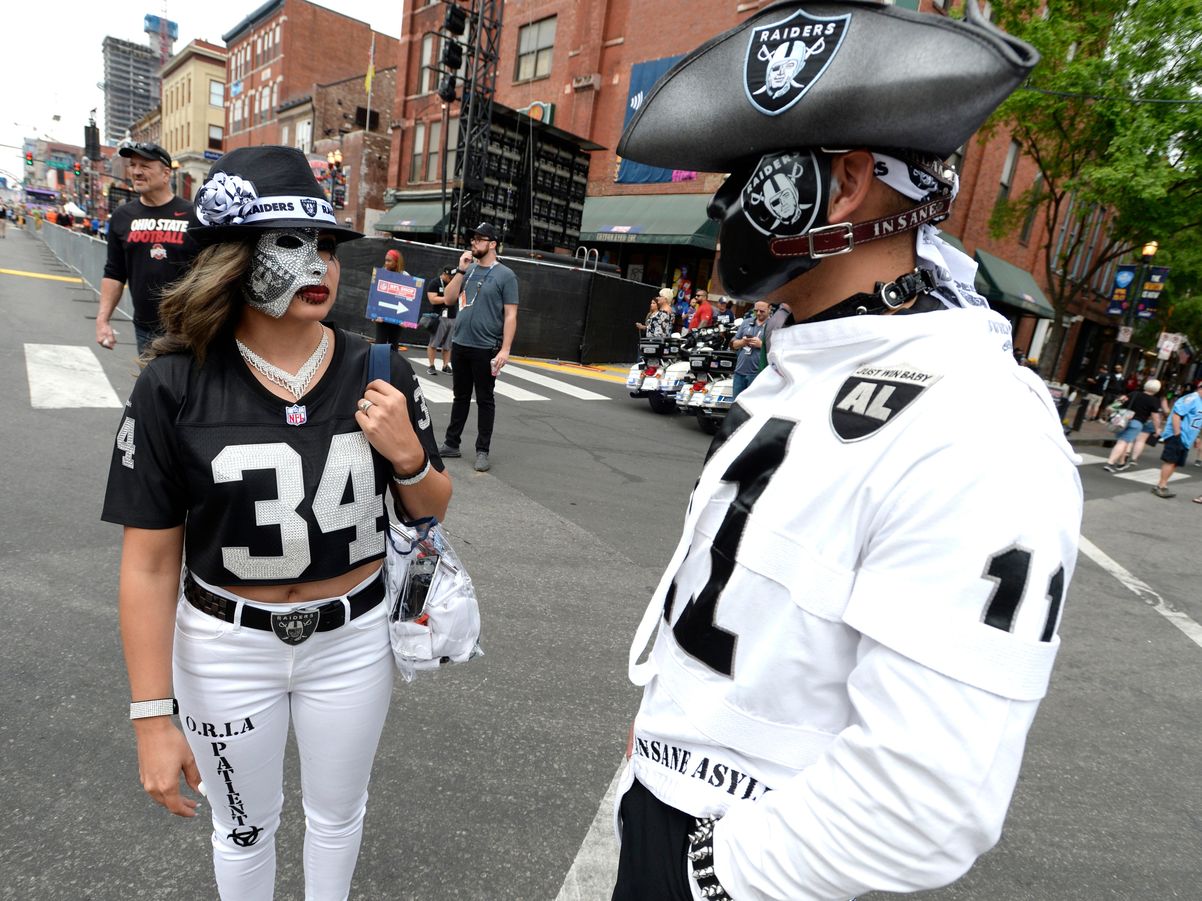 Raiders fans Stephanie Ramos and Mario Orozco chat on Lower Broadway before the start of the 2019 NFL Draft in Nashville, Tenn., Thursday, April 25, 2019.