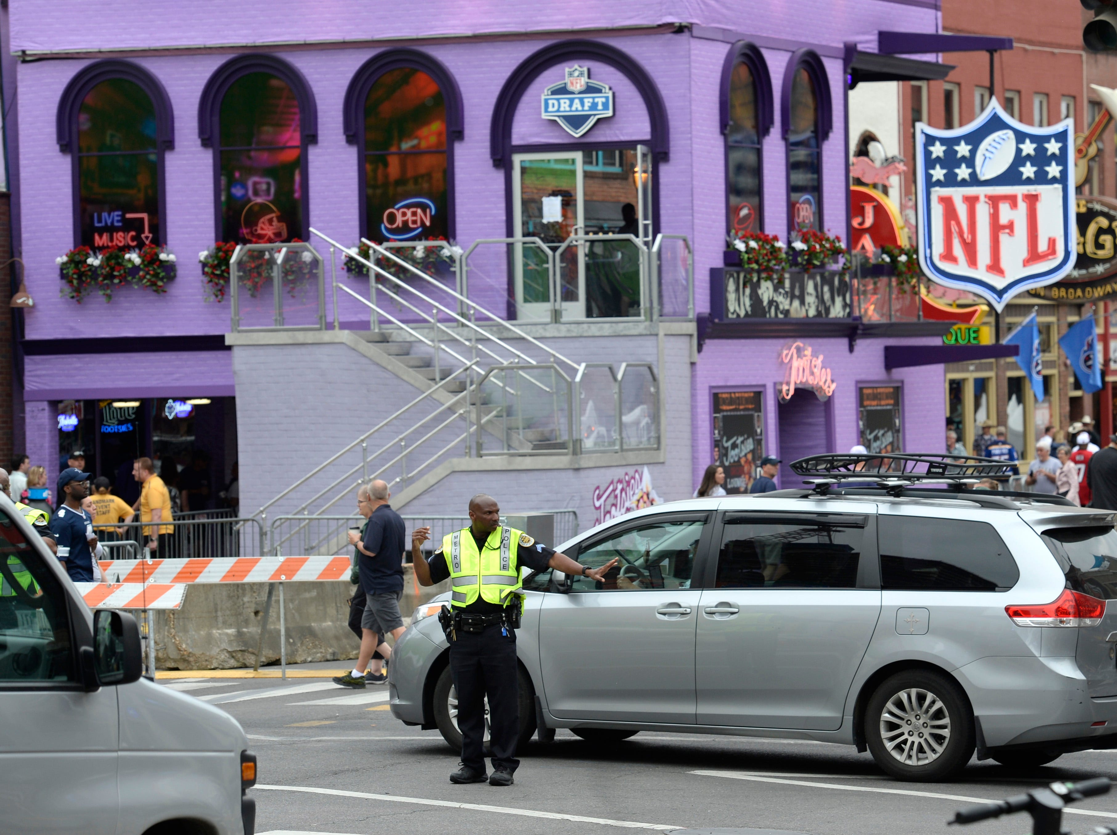 A Metro Nashville police office moves traffic along Fifth Ave. at Broadway before the start of the 2019 NFL Draft in Nashville, Tenn., Thursday, April 25, 2019.