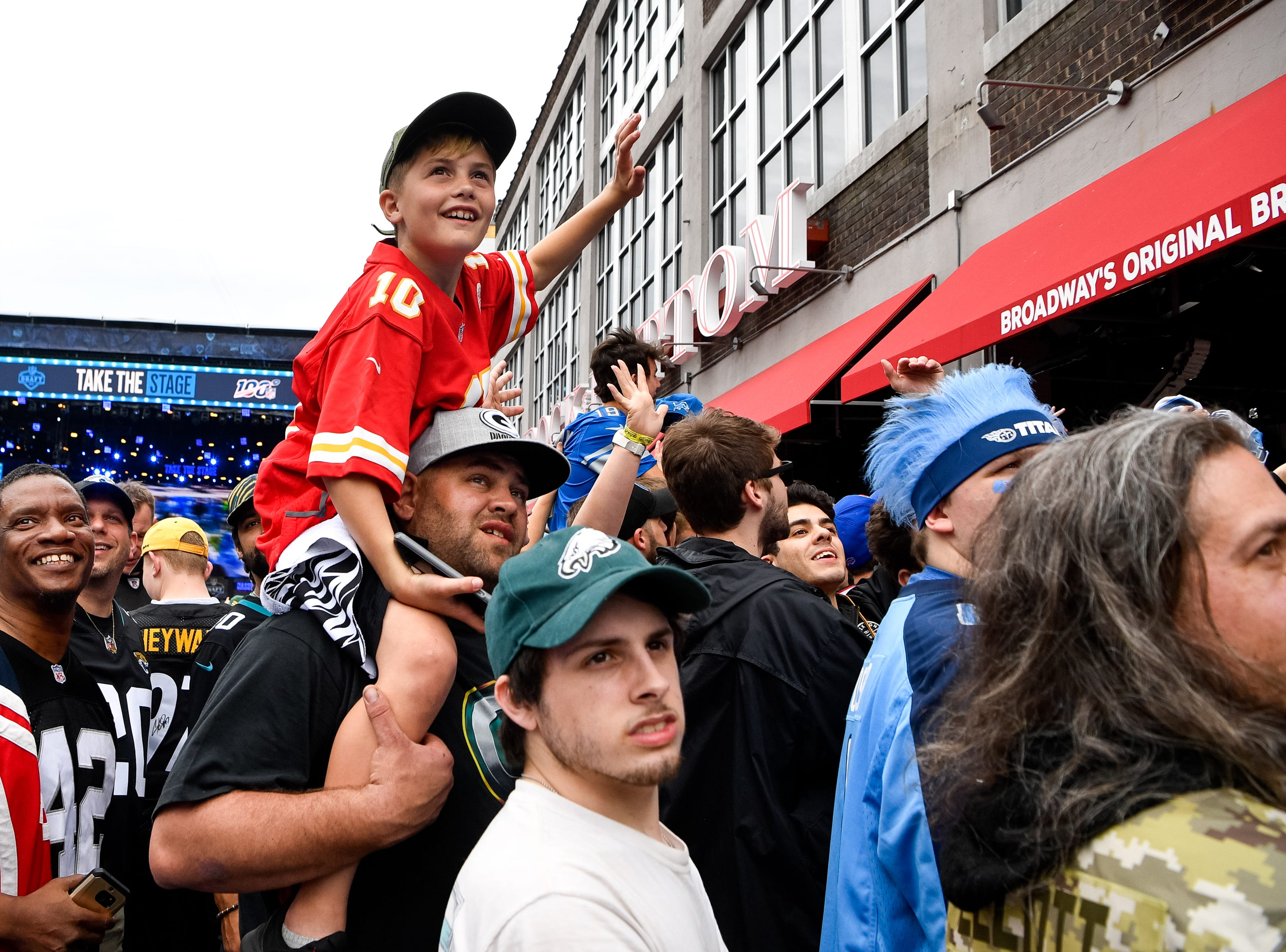 Grady Phelps, 9, sits on his father, Michael Phelps', shoulders to watch himself on TV along Lower Broadway during the NFL Draft Thursday, April 25, 2019, in Nashville, Tenn.