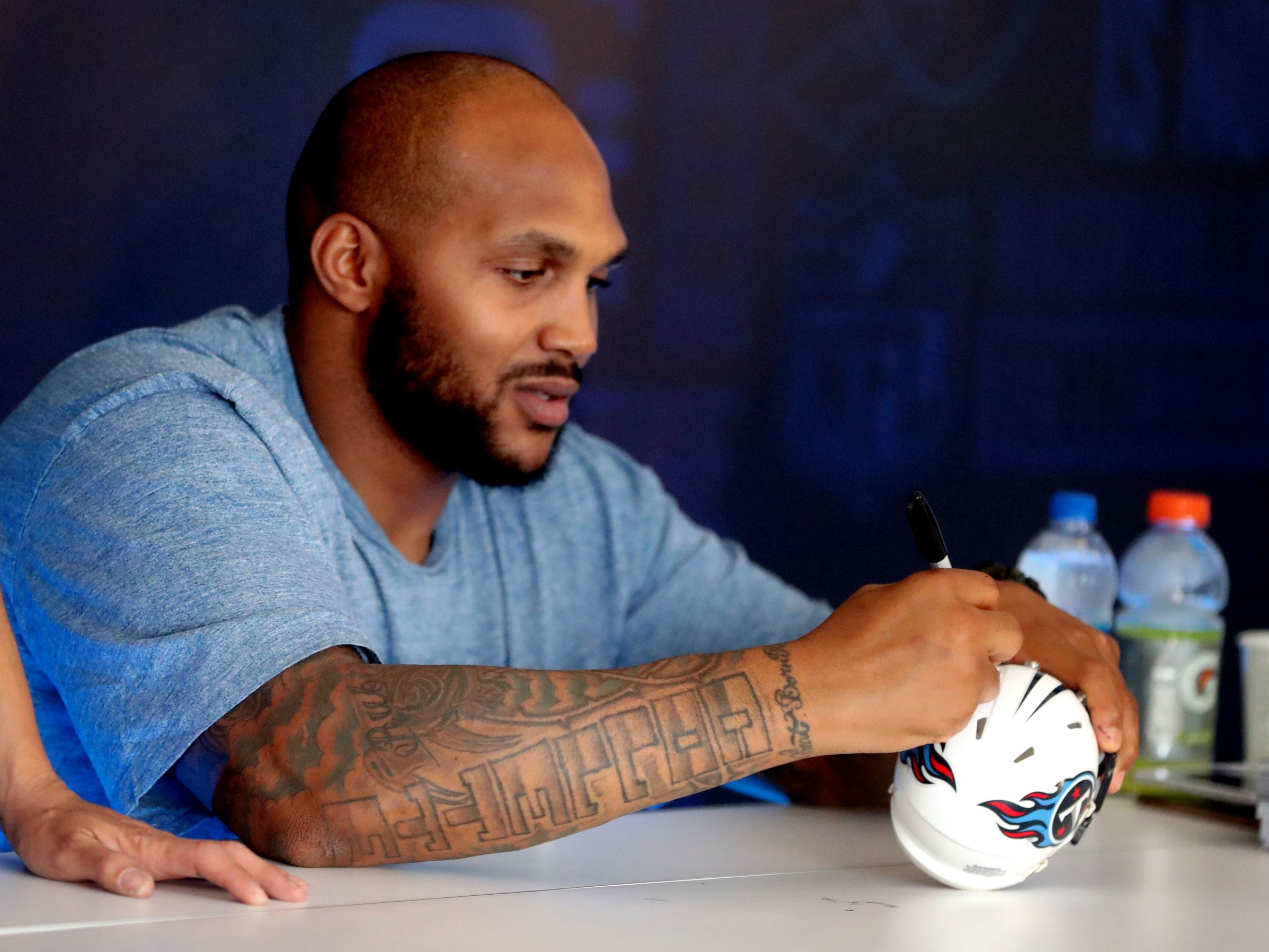 Titan Jurrell Casey signs a small helmet for Alex Gornik at the Autograph stage at the NFL Draft Experience, at Nissan Stadium on Thursday, April 25, 2019, in Nashville, Tennessee.