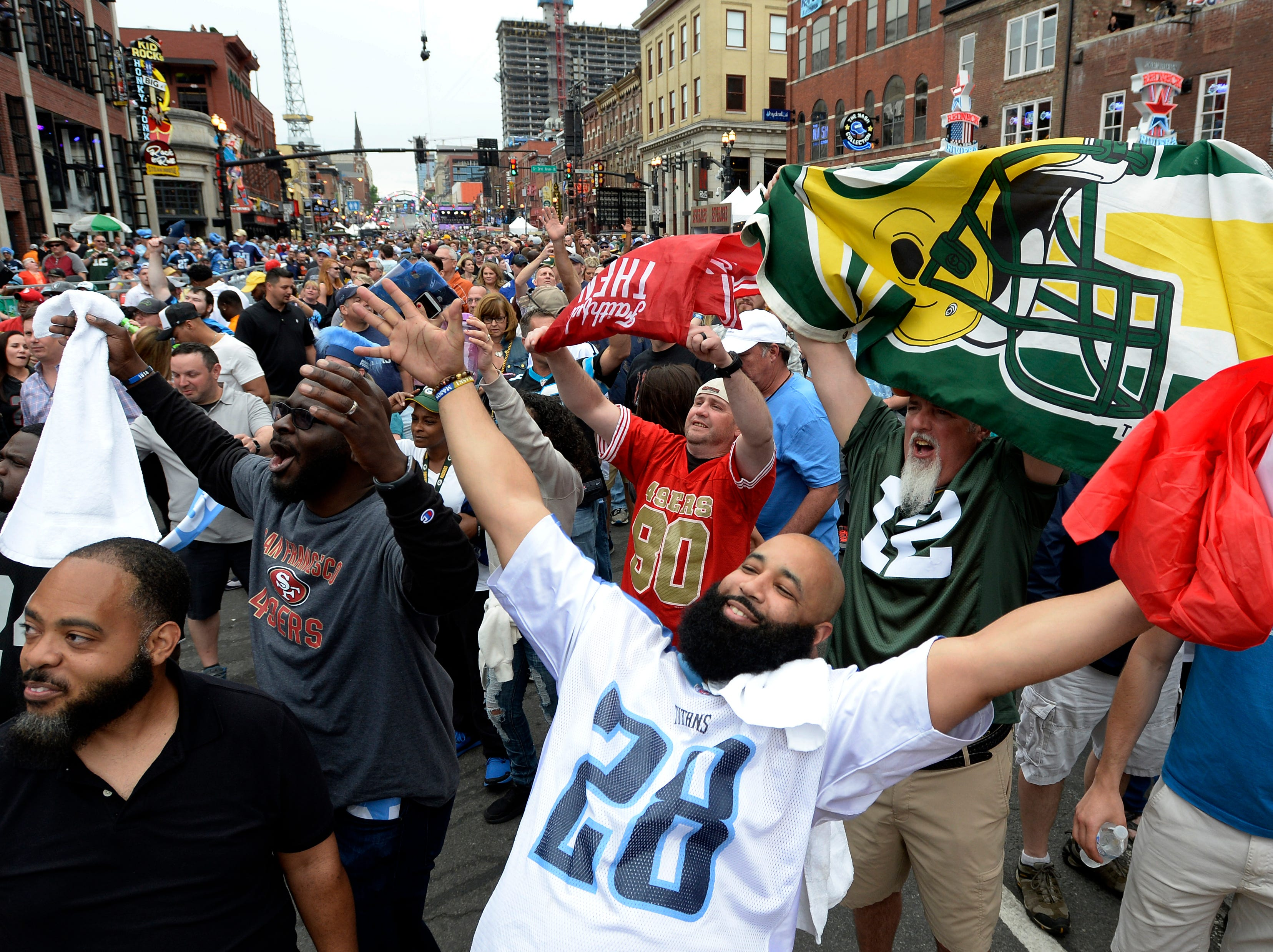 Tennessee Titans fan, Khayree Northcross, bottom center, celebrates on Lower Broadway as he and other fans wait for the start of the of the NFL Draft on Thursday, April 25, 2019, in Nashville, Tenn.