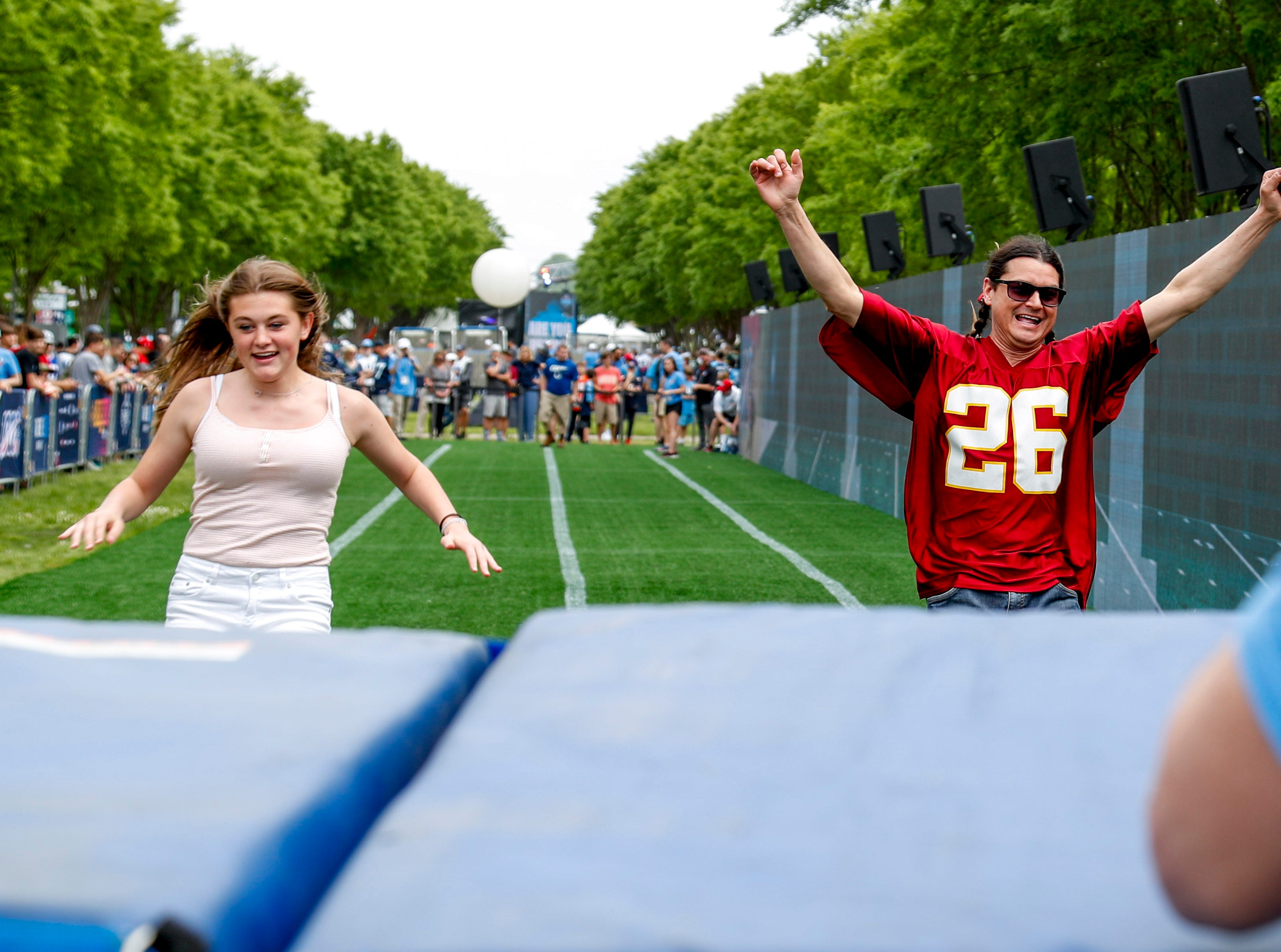 Fans celebrate when running into the giant pads at the end of the 40 yard dash during the NFL Draft Experience at Nissan Stadium in Nashville, Tenn., on Thursday, April 25, 2019.