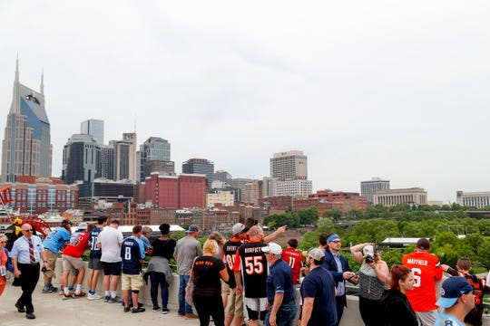 Fans of a multitude of teams hang out on the bridge and look at whats below during the NFL Draft Experience at Nissan Stadium in Nashville, Tenn., on Thursday, April 25, 2019.