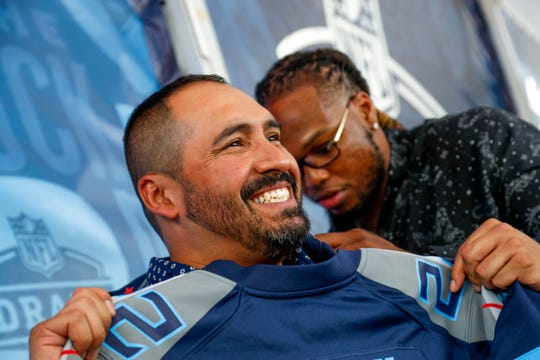 Retired SFC Ralph Rodriguez from Clarksville smiles while Derrick Henry signs jerseys for his family on his back during the NFL Draft Experience at Nissan Stadium in Nashville, Tenn., on Thursday, April 25, 2019.