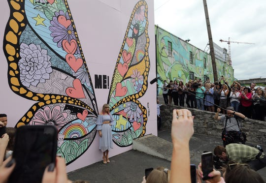 Taylor Swift poses for photos by a butterfly mural in the Gulch during at an appearance in Nashville, Tenn., on Thursday, April 25, 2019.