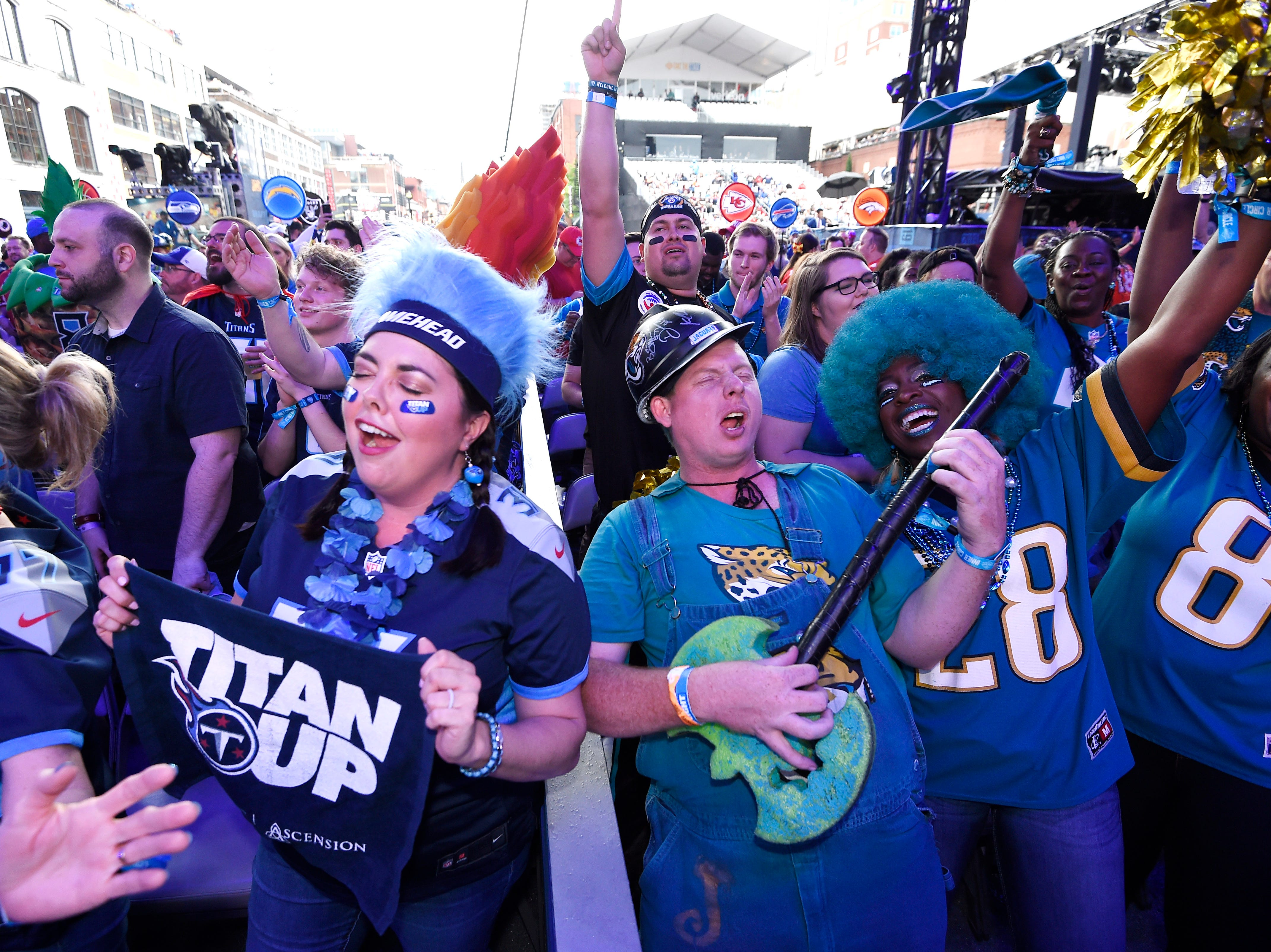 Titans fans dance next to Jaguars fans as Moon Taxi performs before the first round of the NFL Draft Thursday, April 25, 2019, in Nashville, Tenn.