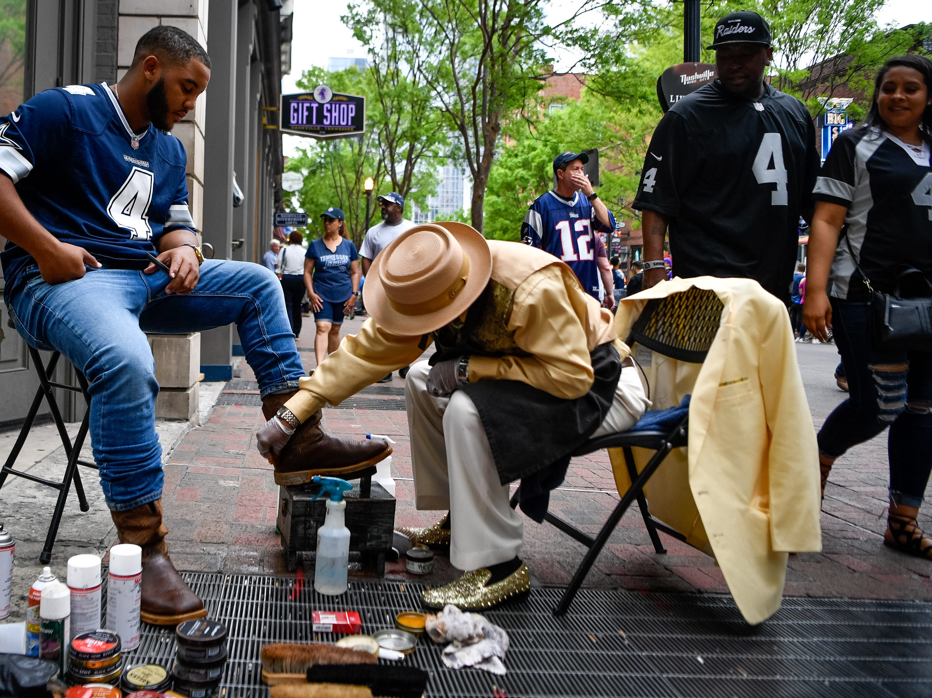 Clete Bridges shines David Prince's boots just off Lower Broadway during the NFL Draft Thursday, April 25, 2019, in Nashville, Tenn.