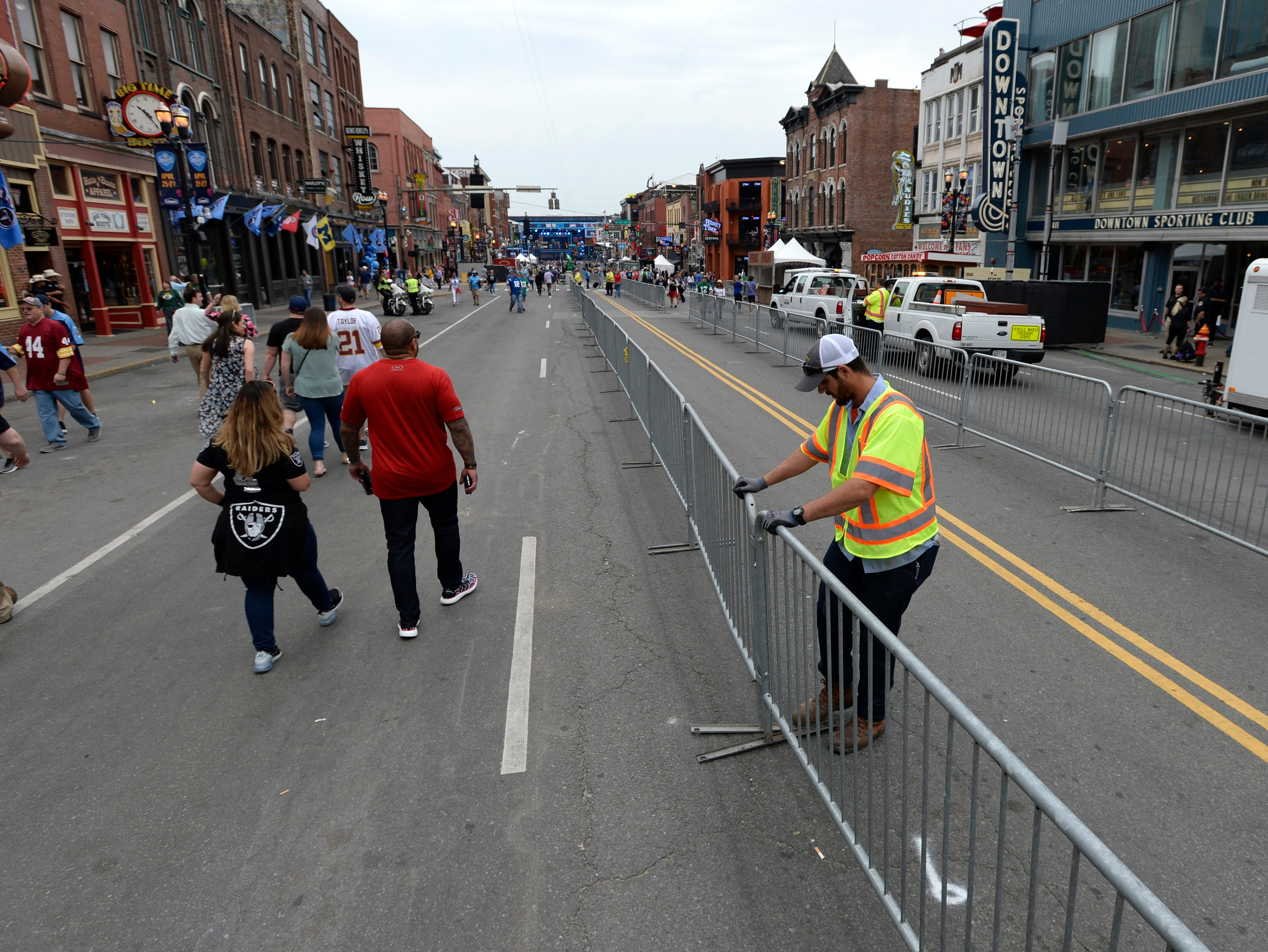 A city worker puts up a barrier for a lane of traffic for the the 2019 NFL Draft on Lower Broadway in Nashville, Tenn., Thursday, April 25, 2019.