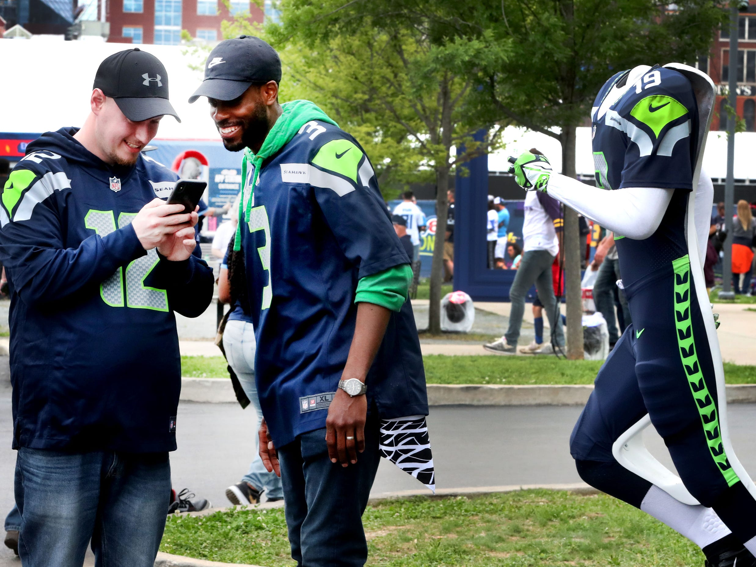 Chris Chambers, left and Marcus Wilson, right look at a picture that Chambers took of Wilson behind the Seattle Seahawk uniform at the NFL Draft Experience, at Nissan Stadium on Thursday, April 25, 2019, in Nashville, Tennessee.