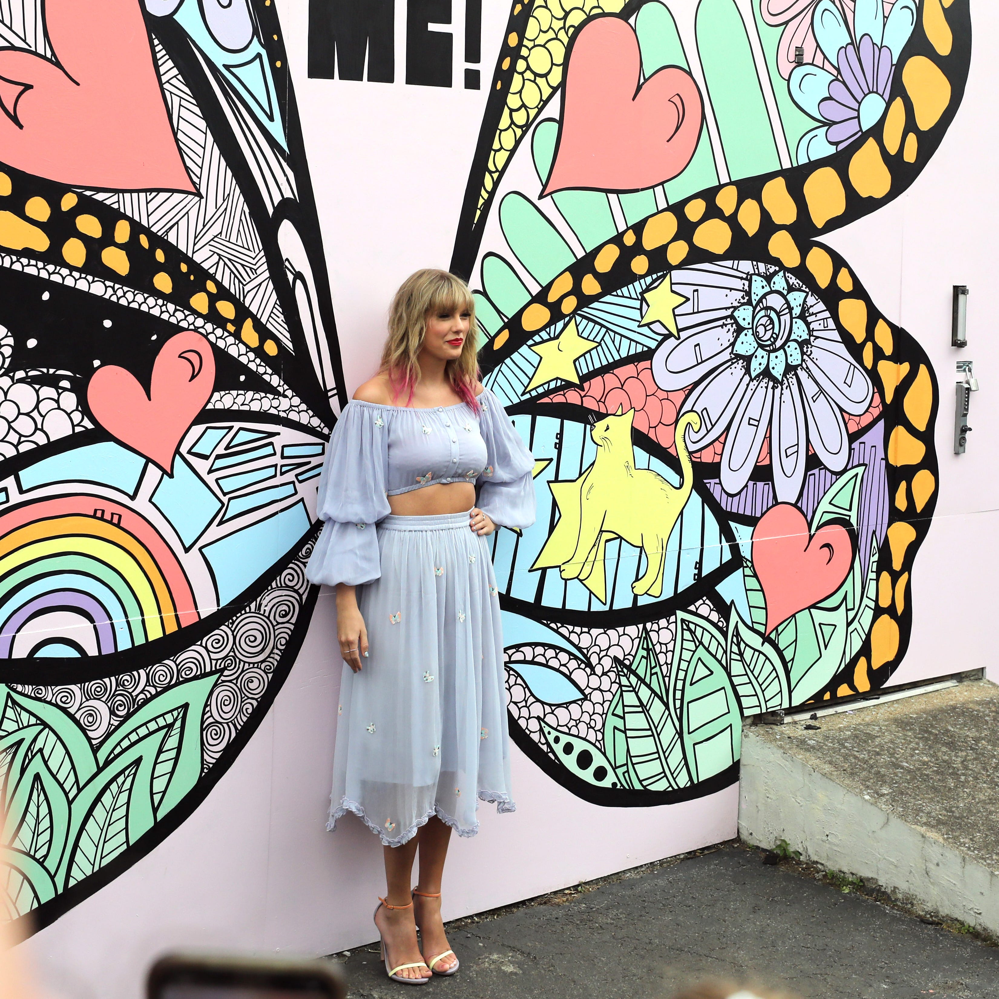 Taylor Swift poses at a butterfly mural in...