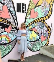 Taylor Swift poses at a butterfly mural in Nashville, Tenn., Thursday, April 25, 2019.