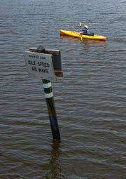 A kayaker paddles past Baker Park along the Gordon River, Thursday, April 25, 2019, in Naples.