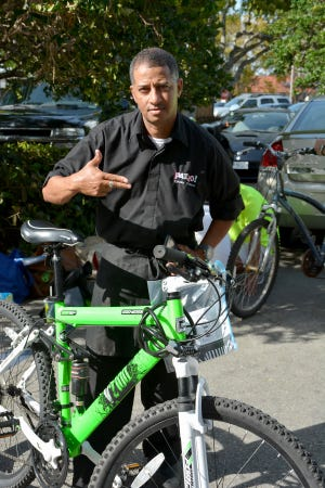 Restaurant worker Coco Zdravkovski shows off his bike, outfitted with safety lights. In 2015 volunteers from the Naples Pathways Coalition installed headlights and taillights on 90 bicycles belonging to Fifth Avenue restaurant workers.