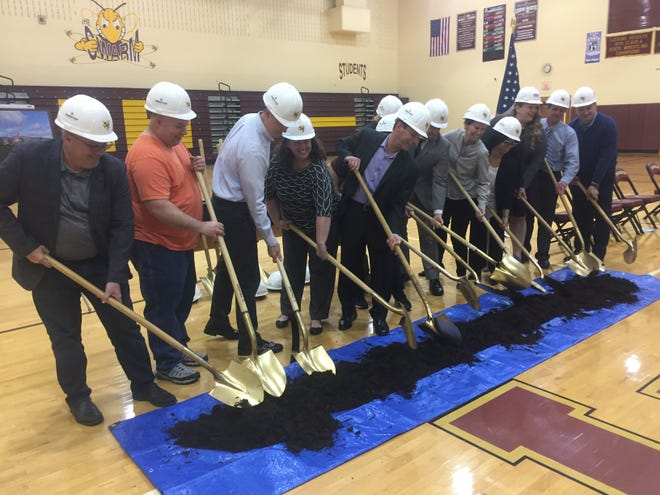 Officials symbolically turn some mulch in the present Licking Heights High School gymnasium.