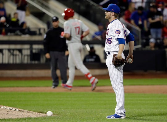 New York Mets relief pitcher Jacob Rhame, right, reacts as Philadelphia Phillies' Rhys Hoskins runs the bases after hitting a two-run home run during the ninth inning of a baseball game, Wednesday, April 24, 2019, in New York.