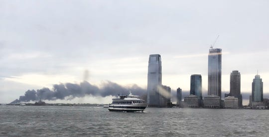 Smoke rises from a fire and floats past high rise buildings in Jersey City, N.J., from a fire at the Sims Metal Management scrap metal yard, Thursday, April 25, 2019. It is unclear how the fire started and there are no immediate reports of injuries.