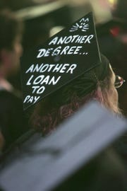 Cat Graney, of Bloomingdale, has a note on her hat that fits a family joke. Graney has a bachelor degree in History and a masters in Modern European History and has returned to school and is now graduating with a certificate in computer animation. Bergen Community College Graduation Ceremony 2006.