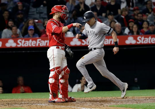 New York Yankees' Tyler Wade, right, scores on a single from DJ LeMahieu during the ninth inning of a baseball game against the Los Angeles Angels Wednesday, April 24, 2019, in Anaheim, Calif.