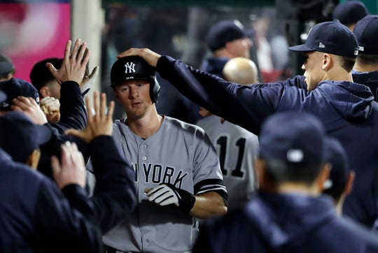 New York Yankees' DJ LeMahieu, facing camera, gets high-fives in the dugout after scoring on a passed ball during the sixth inning of a baseball game against the Los Angeles Angels, Wednesday, April 24, 2019, in Anaheim, Calif.
