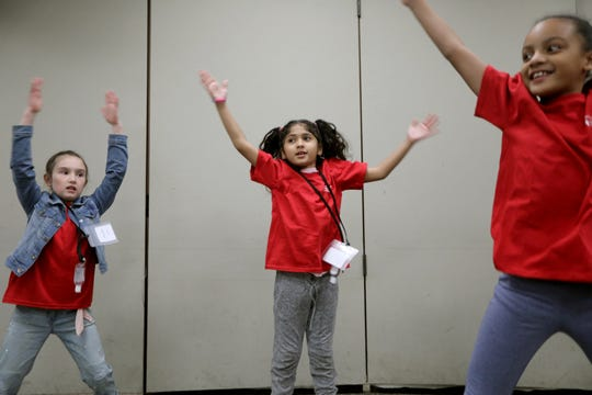 Aaliyah Medina (center), Lucille Algieri (left) and Desiree Vaughan do jumping jacks,  at Morristown Medical Center, during the Bring your Kids to Work program. Thursday, April, 25, 2019