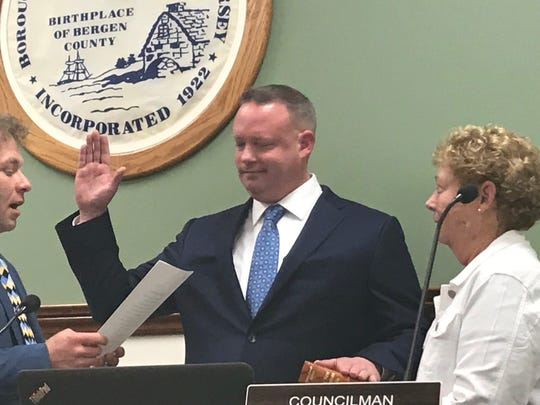 Brian Clancy is sworn in as the new police chief of New Milford as New Milford Mayor Michael Putrino, left, swears him in while Clancy's mom, Maureen holds the Bible.
