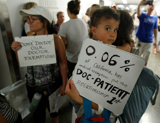 Chelsea Lydell holds her son, Joseph, 4, as she joins hundreds of others waiting to get into a legislative committee to oppose a proposal to give state public health officials instead of local doctors the power to decide which children can skip their shots before attending school, at the Capitol Wednesday, April 24, 2019, in Sacramento, Calif.