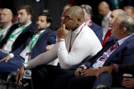 Richard Seymour, former NFL football defensive tackle who played for the New England Patriots and Oakland Raiders, listens during a keynote speech by former New Orleans Saint kicker and Hall of Fame enshrinee Morten Andersen during the Betting On Sports America conference, Thursday, April 25, 2019, in Secaucus, N.J. (AP Photo/Julio Cortez)