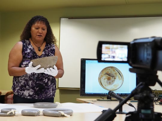 Hopi artist Gwen Setalla gently examines a piece of prehistoric Mimbres pottery in a session where five Native American artists were recorded on video giving their interpretations of the designs and meanings of the pottery.