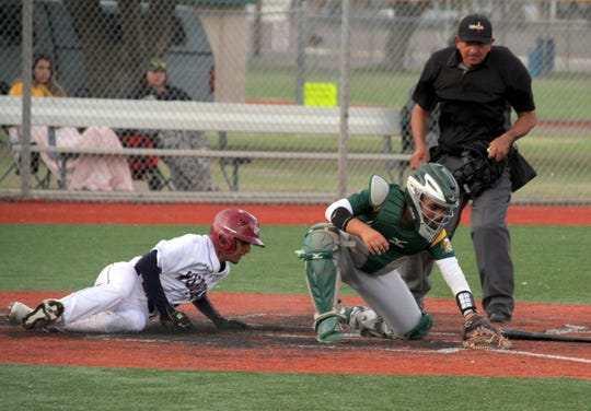 Wildcat base runner Isaiah Chavez slips past the Mayfield catcher to score a Deming run on a well-executed suicide squeeze play during Tuesday's 11-6 Wildcat loss to the Trojans.