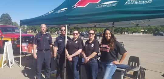 Carlsbad Community Anti-Drug/Gang Coalition Preventionist Lysondra Bartock (right) stands with members of the Carlsbad Police and Fire Departments April 20 at the Household Hazardous Waste Clean Up Day at the Carlsbad Beach.