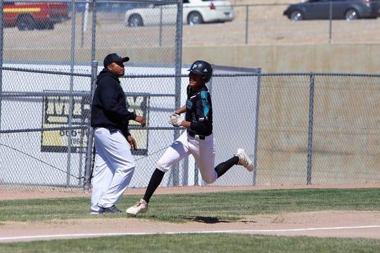 Navajo Prep's Marley Deschiney darts across third base and scores a run against Thoreau during Thursday's District 1-3A game at Farmington Sports Complex.