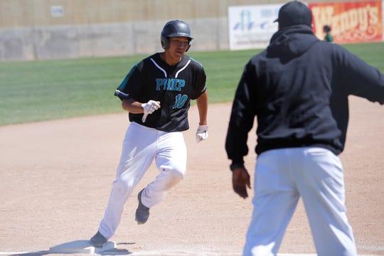 Navajo Prep's Ian Whitehorse runs across third base and scores a run against Thoreau during Thursday's District 1-3A game at Farmington Sports Complex.