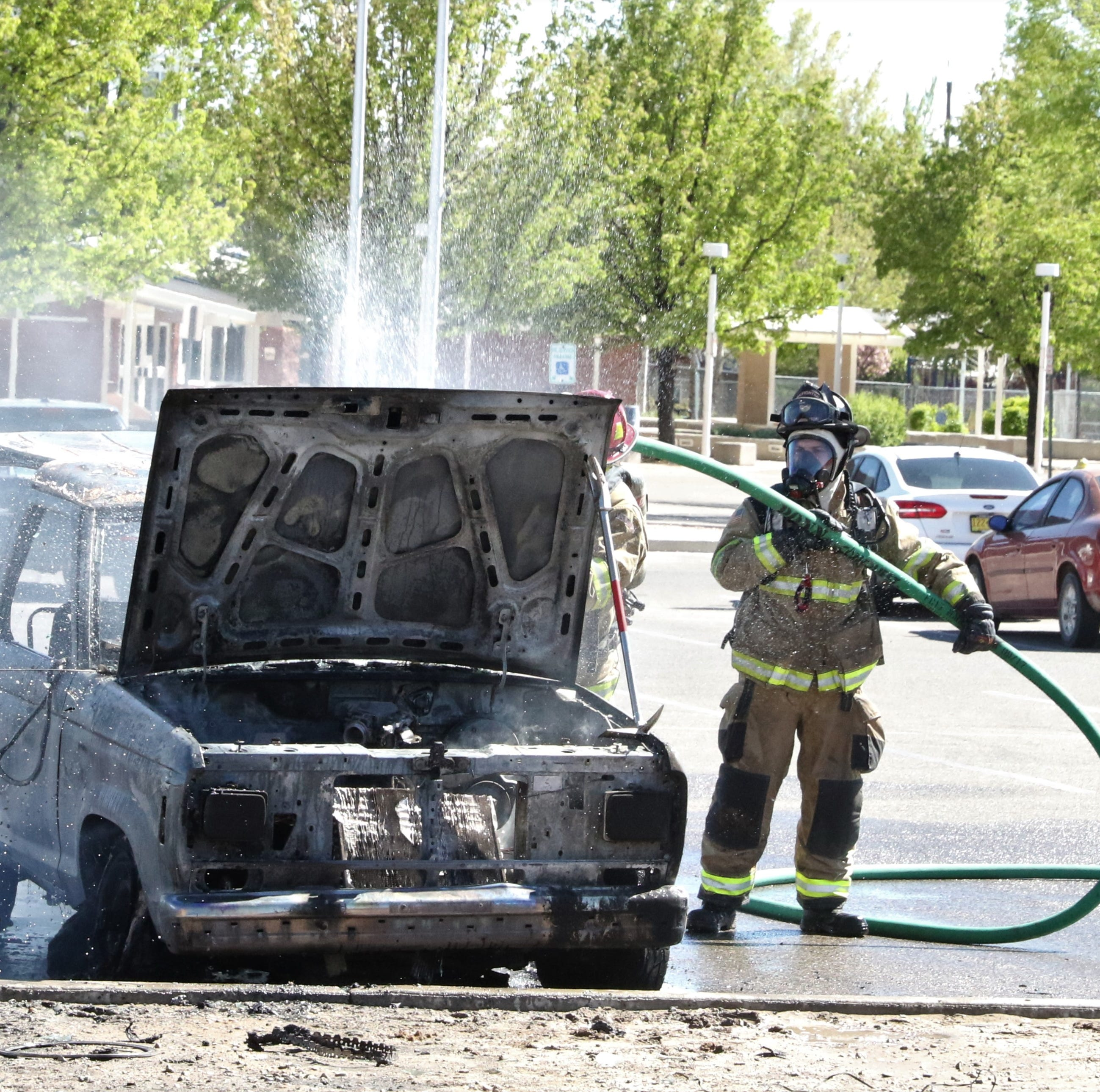 Firefighters extinguish car fire behind movie theater