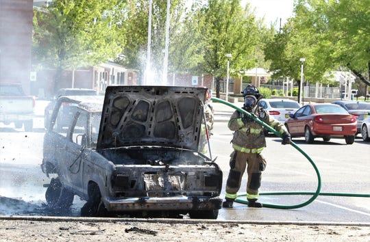 A Farmington firefighter extinguishes a fire in a car, Thursday, April 25, 2019, in Farmington.