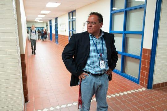Principal Mario Zuniga stands in the hallway of Socorro High School during a break between classes.