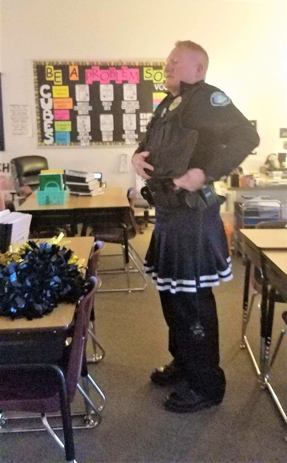 """""""Is it my gun belt too big, or is this skirt too small for me?"""" Chief Hooker prepares for an assembly to encourage students to do well on test day."""
