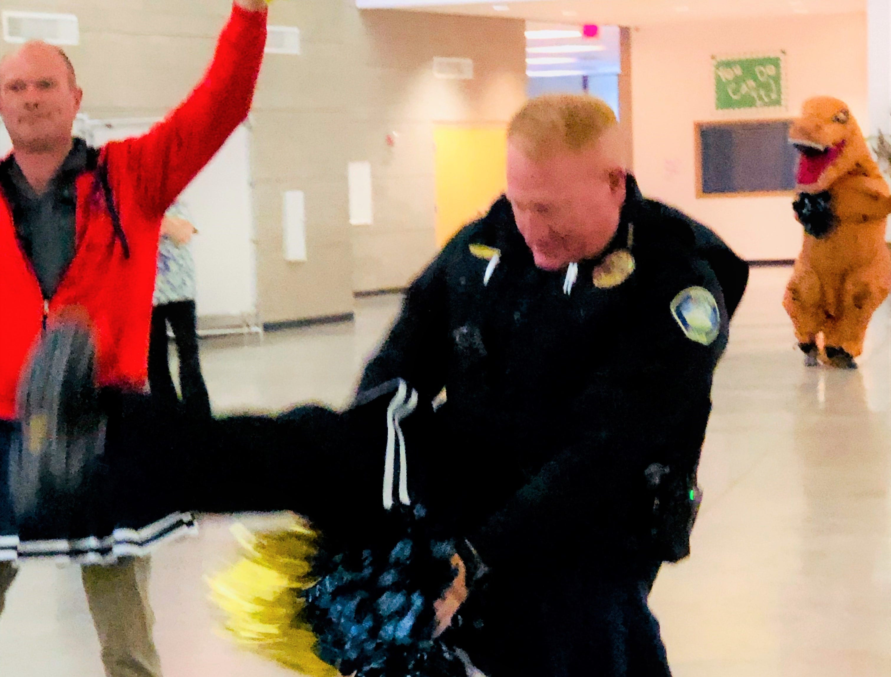 And a one, and a two...Cheer Squad Chief Hooker, school board president Luther Light (left) shake their pom-poms during a high kicking routine to encourage students during an a pep assembly at Ruidoso Middle school. It appears that T-Rex is not only photo bombing the two, but seems to be getting a kick out of their routine.