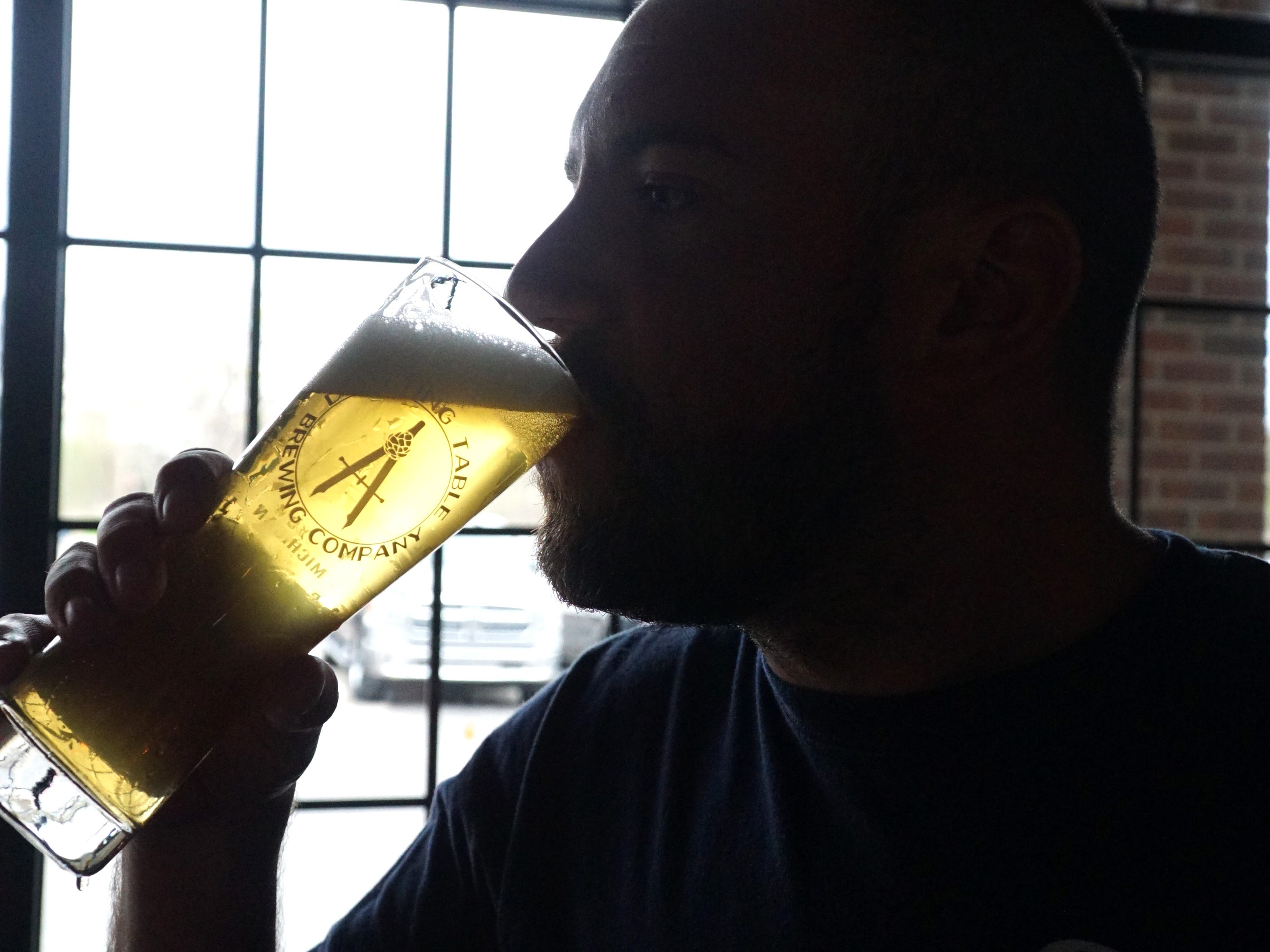 Aaron Rzeznik takes a sip of the Drafting Table's Professional Pils.