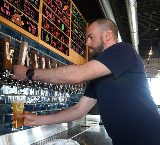 Wixom's Drafting Table brew-pub owner Aaron Rzeznik draws a pint of their award-winning Professional Pils at their Pontiac Trail location.