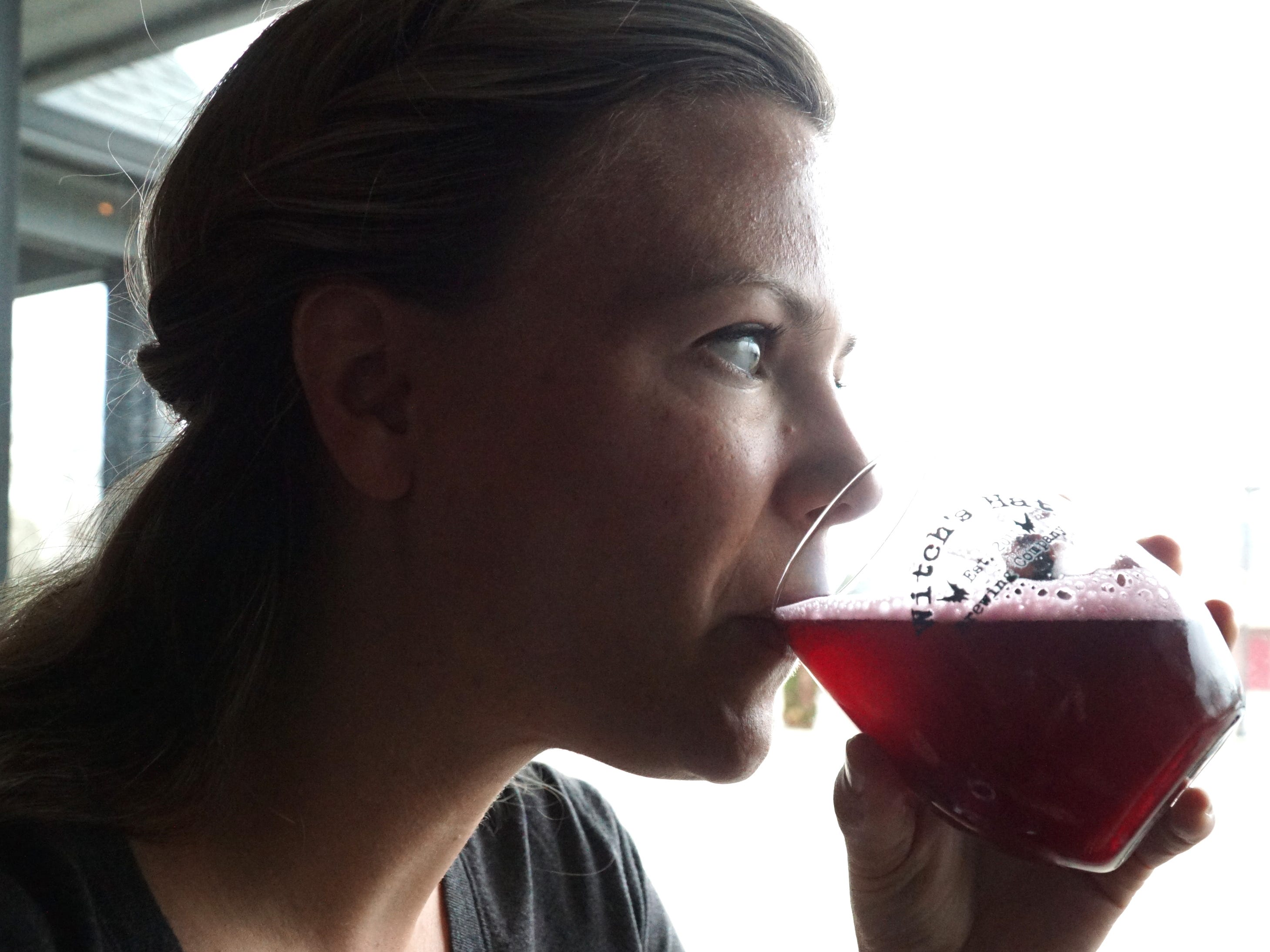 Erin Cottongim takes a sip of Witch's Hat Brewing Company's Blueberry-Lemonade gose brew on April 25. Cottongim and her husband Ryan co-own Witch's Hat.
