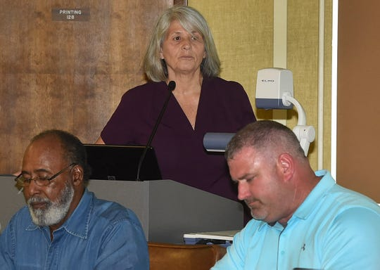 Nichole Boudreaux (background) presents a proposal during a St. Landry Parish School Board public hearing for a proposed French immersion school in Sunset. Listening to Boudreaux are board members Anthony Stadnberry (left) and Josh Boudreaux. Fred Herpin photo.