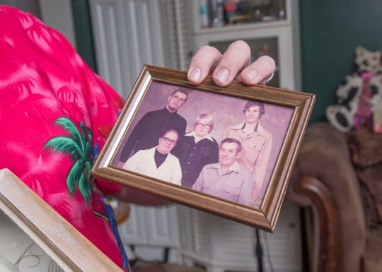 Doug Janousek shows old photos of his family at his home in Gulf Breeze on Thursday. Janousek, who is going to have preemptive pancreatic surgery, lost his grandfather, father and oldest brother to pancreatic cancer and is at high risk himself.