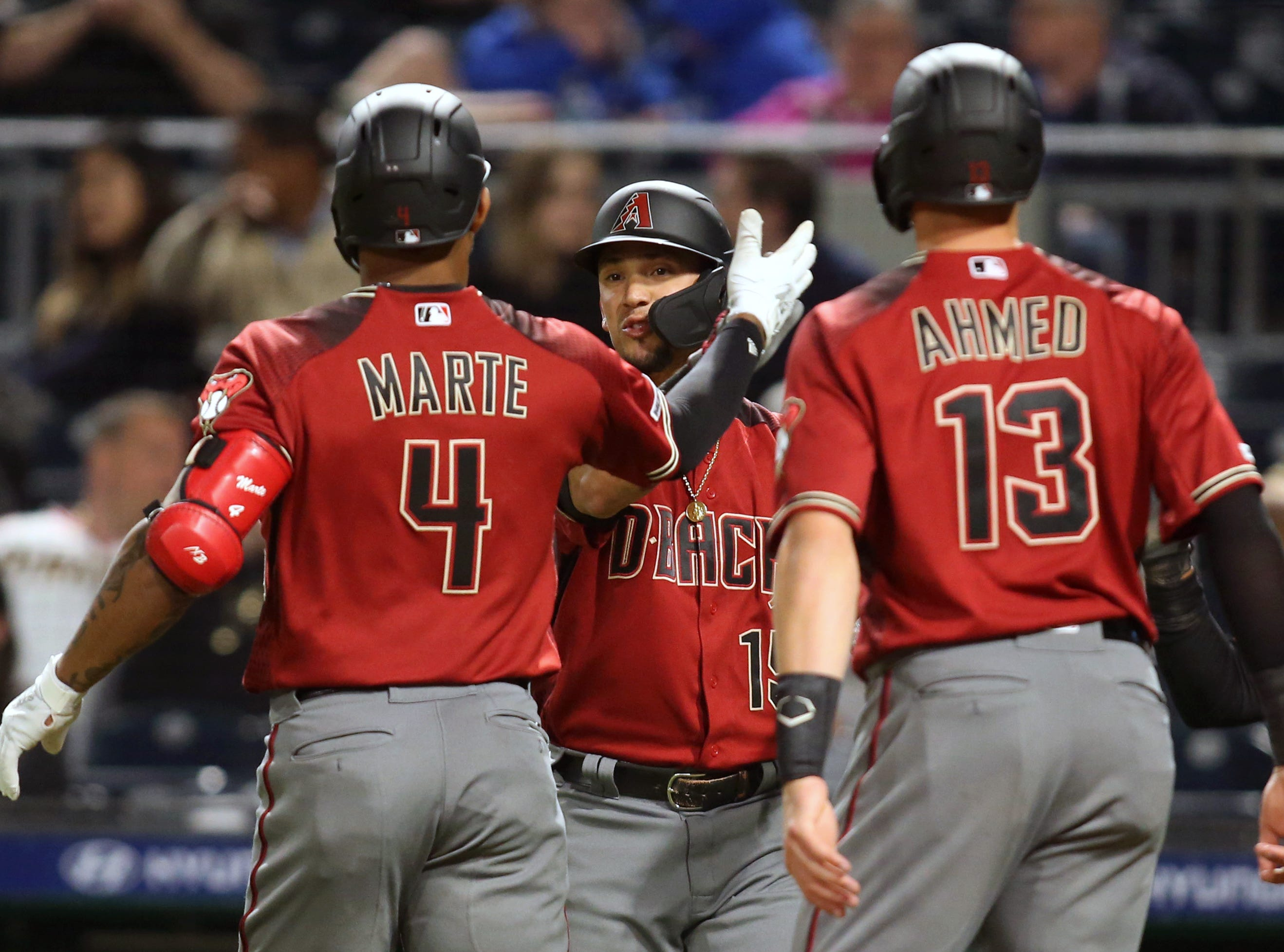 Apr 24, 2019; Pittsburgh, PA, USA;  Arizona Diamondbacks center fielder Ketel Marte (4) celebrates with third baseman Ildemaro Vargas (15) and shortstop Nick Ahmed (13) after hitting a three run home run against the Pittsburgh Pirates during the eighth inning at PNC Park. Mandatory Credit: Charles LeClaire-USA TODAY Sports