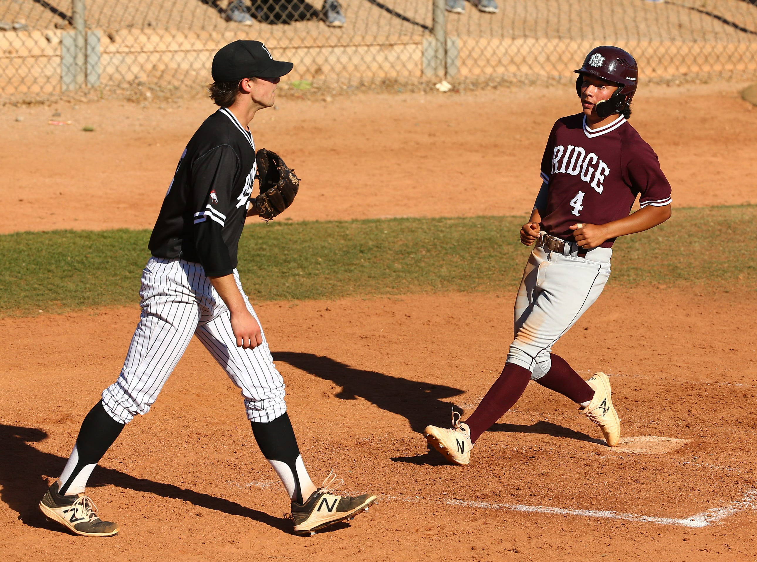 Mountain Ridge High's Travis Warinner (4) scores against Brophy Prep in the third inning on Apr. 24, 2019 in Phoenix, Ariz.