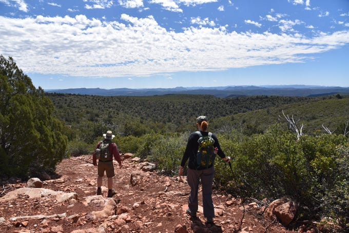 Hikers walk the rough road to Cedar Mesa.