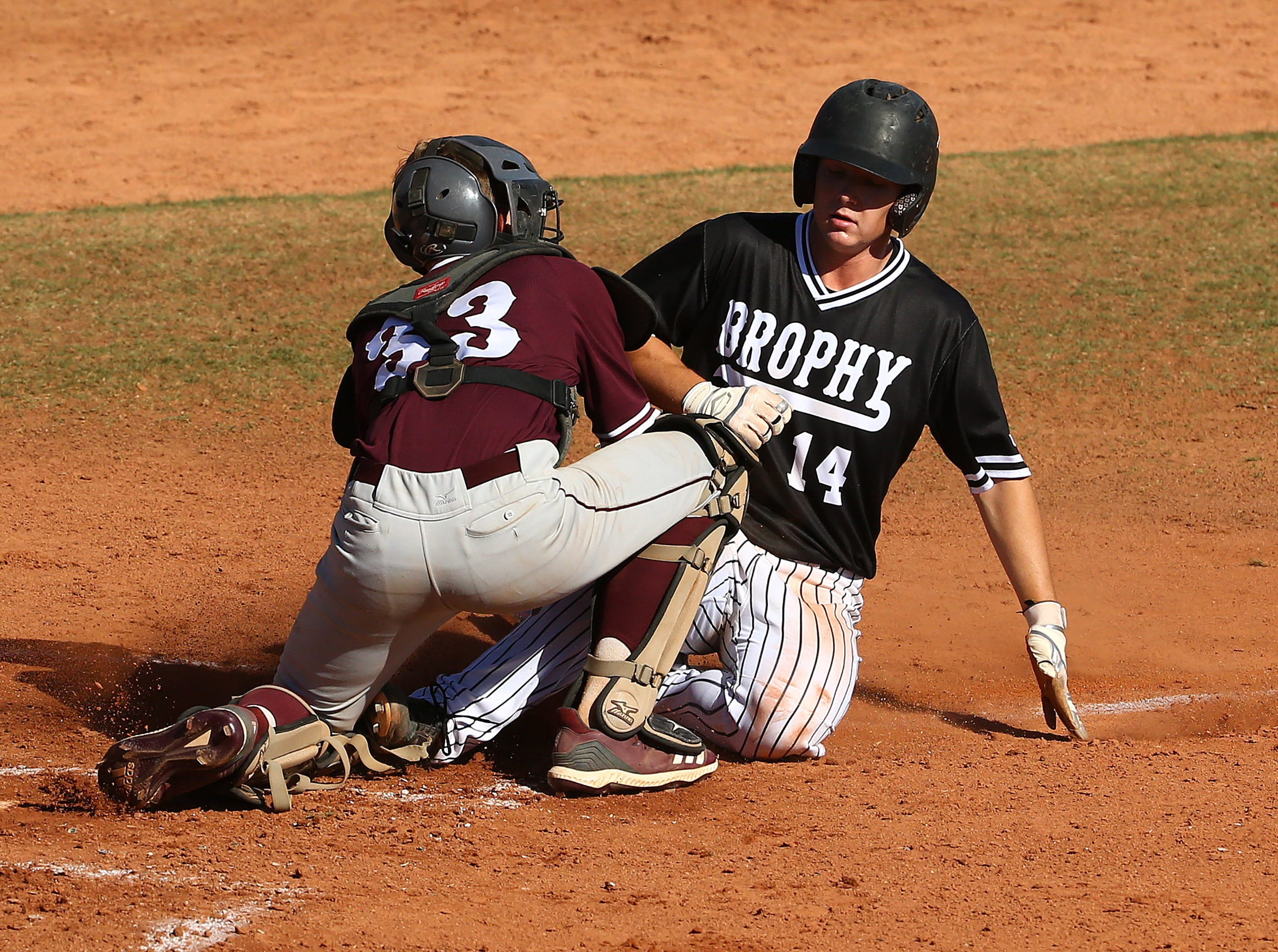 Mountain Ridge High catcher Olson Garrett (33) tags-out Brophy Prep's Will Worthington (14) in the first inning on Apr. 24, 2019 in Phoenix, Ariz