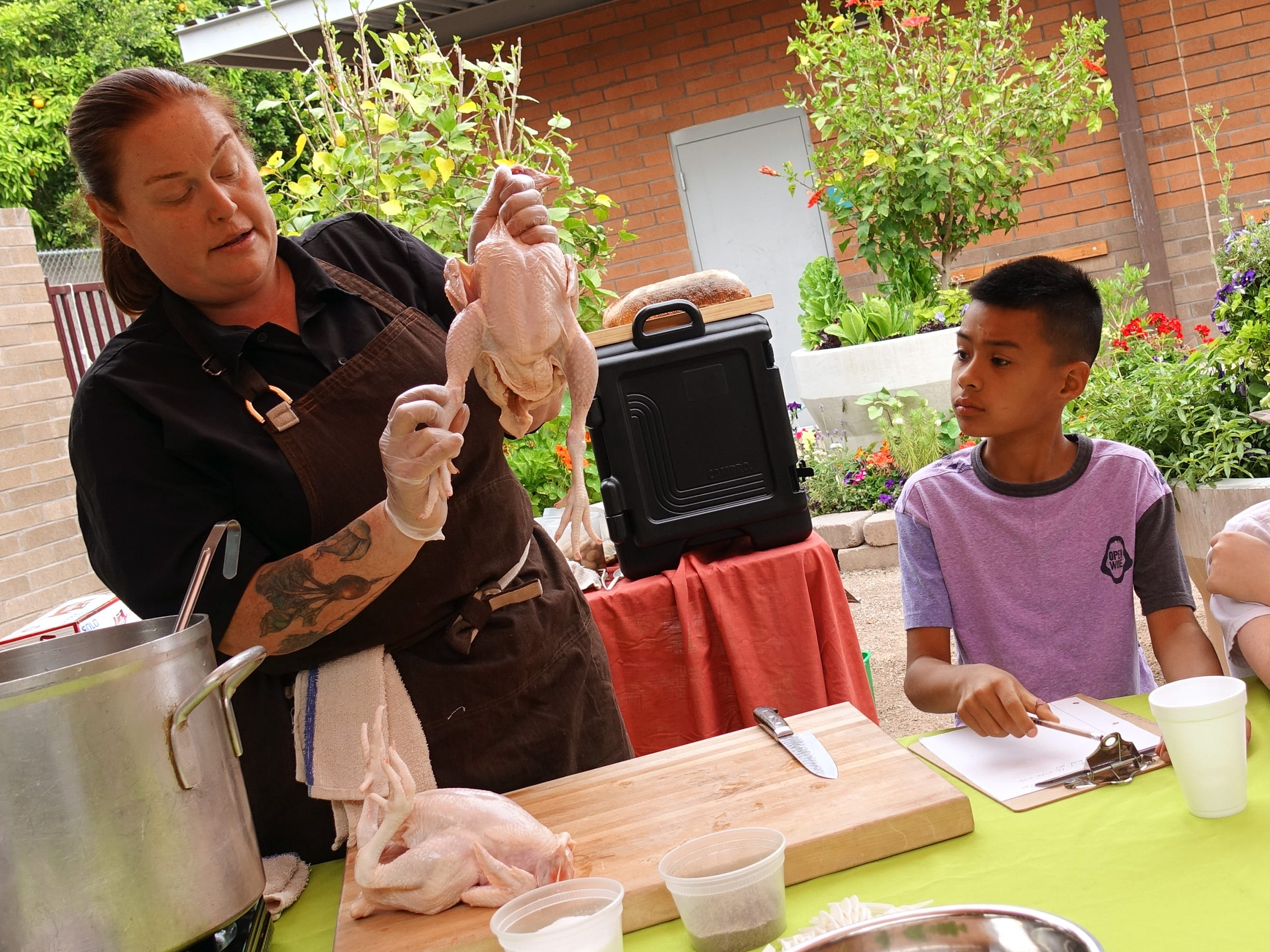 Charleen Badman of FnB demonstrates how to break down a chicken for fourth-graders at Echo Canyon School in Scottsdale.