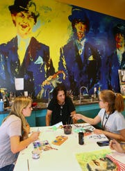 Alice Cooper visits with Courtney Stimmler and Brin Joyner (right, both age 12) as they paint in the art studio at Alice Cooper's The Rock Teen Center on Apr. 23, 2019 in Phoenix, Ariz.