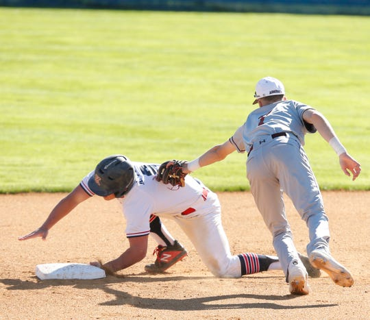 Arlington shortstop Perry Racanello applies a tag to Ketcham's Anthony Vose as he lunges for the second base bag during Wednesday's game.