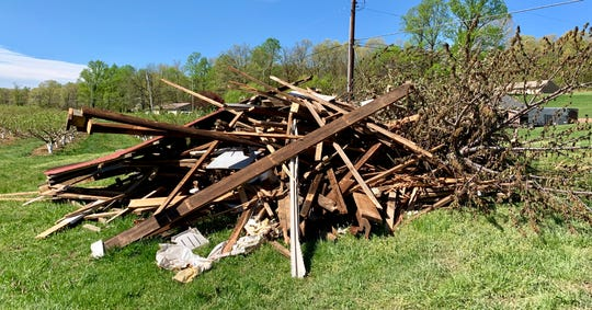 Debris from a barn at Andrews Farm in St. Thomas Township and tree branches sit near what's left of the structure following a tornado that touched down in the area the evening of Friday, April 19. The wind funnel sent debris flying through farm, damaging trees and blowing them over onto the ground.